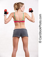Attractive thirties caucasian woman lifting dumbells
