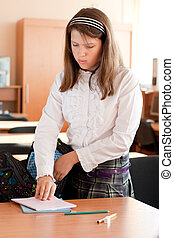 Preteen schoolgirl packs things into her bag after lesson