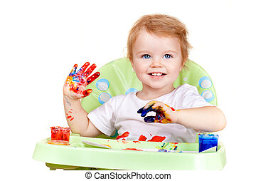 baby girl with blue eyes creates picture sitting at table...