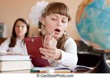 Cute preteen schoolgirl is making make-up during lesson at...