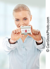 Businesswoman holding house model - Young businesswoman...