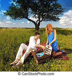 picnic - man and woman on picnic in green grass