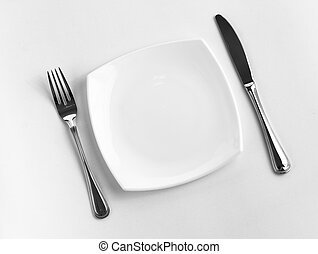 Place setting for one person. Knife, square white plate and...