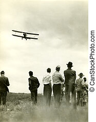 Bi wing airplane - Men watching flight of bi wing airplane...
