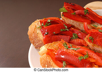 Side view of roasted red pepper and basil bruschetta on a...