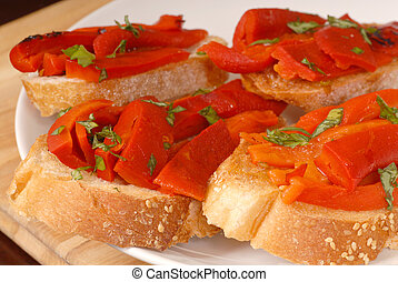Roasted red pepper and basil bruschetta on a white plate - A...