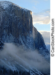El Capitan illuminated by rising sun on a misty morning - El...