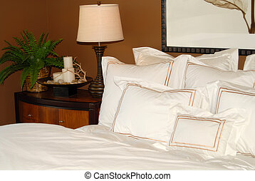 Bed with white bedspread and nightstand - Bedroom with...