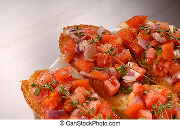 Tomato and onion bruschetta with thyme - A plate of tomato...