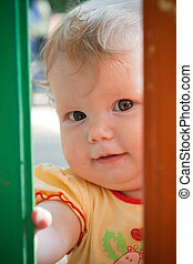 Baby-girl looking into fence hole