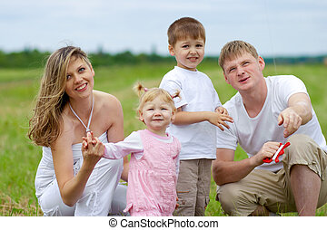 Happy family fly a kite together in summer field - Happy...