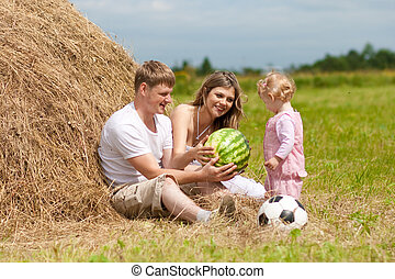 Happy family has fun in haystack to