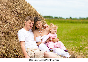 Happy family in haystack or hayrick - Happy family in...