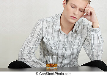 Attractive young guy drinking whiskey - depressed
