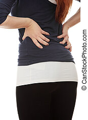 Young woman with pain in her back. Isolated