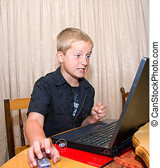 angry computer boy - boy sitting at laptop showing...