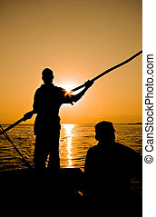 dhow rower - silhouette of rower with pole on a dhow backlit...