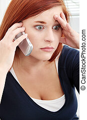 Bad news - Young woman getting bad news by phone