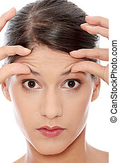 Woman with the wrinkles on her forehead