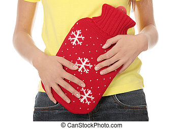 Female holding red hot water bottle or hot water bag on...