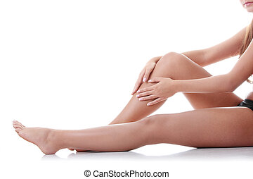 Woman holding on leg. Isolated on white