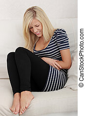 Blond woman with stomache issues - Young beautiful blond...