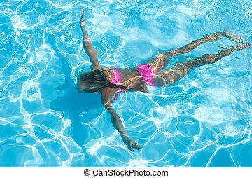 girl enjoys an underwater swim