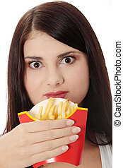 Young woman eating french fries - Young woman eating fries...