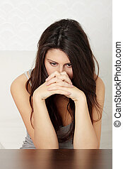 A worried and afraid young woman sitting on sofa.