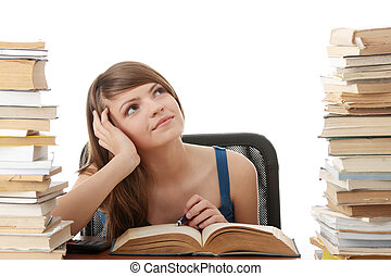 Teen girl learning at the desk, with lot of books around,...