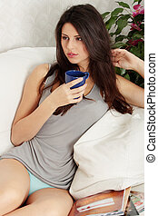 Young beautiful woman resting on sofa