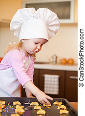 Little girl preparing cookies on kitchen