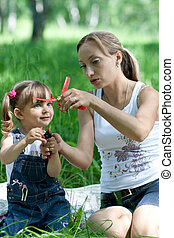 Mother and daughter in jeans with toy outdoor