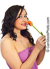 Young woman hold single tulip - Young smiling woman holding...