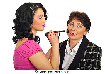 Beautician applying blush on mature face