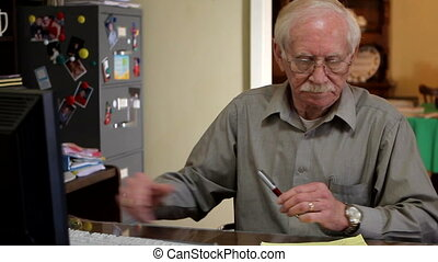 Retiree Home Office - Retiree works at the computer in his...