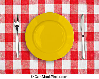 Knife, yellow plate and fork on red checked tablecloth