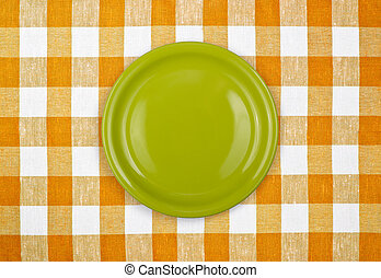 green plate on yellow checked tablecloth