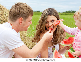 Happy family in haystack feeding mother with watermelon