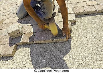 work paving  - man at work paving stones with rectangular