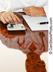 Doctor with a calculator Costing medical practice - Doctor...