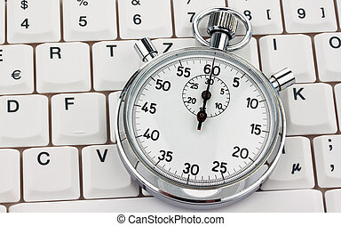 Stop watch on computer keyboard - A stopwatch is on a...