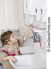 hygiene - little girl with clean hands grabbing paper towel