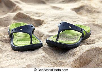 Female slippers on a coast of ocean