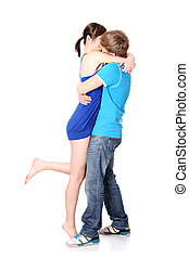 Beautiful young couple kissing against white background