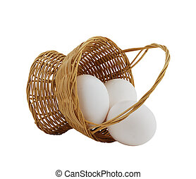 three white eggs spilled from straw interwoven basket...