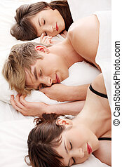 Handsome man lying in bed with two girls - Young handsome...