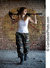 Walking mercenary woman with the rifle on the brick wall...