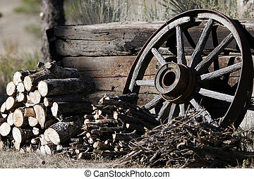 Woodpiles with Wagon Wheel - Stacks of wood and kindling are...