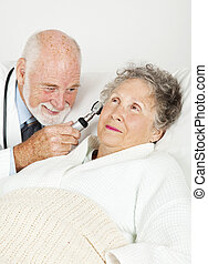 Doctor Examines Hospital Patient - Doctor uses an otoscope...